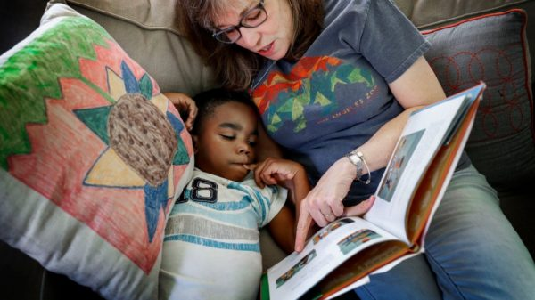 "Carpenter Art Garden volunteer Jane Pate reads ""Last Stop on Market Street"" to after-school student Javion Hicks, 7. (Mark Weber/Daily Memphian)"