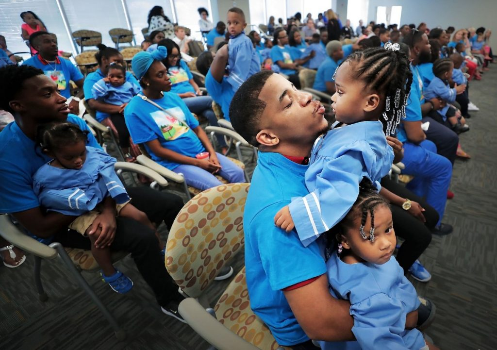 Kevin Broady tries to keep his twin one-year-old girls Serenity Broady and Kennedi Broady (right) entertained during a graduation ceremony for parents and kids in Le Bonheur's Nurse-Family Partnership at the hospital's community outreach center on Aug. 2, 2019. The program connects nurses with first-time pregnant mothers to guide them through early child development. (Jim Weber/Daily Memphian)