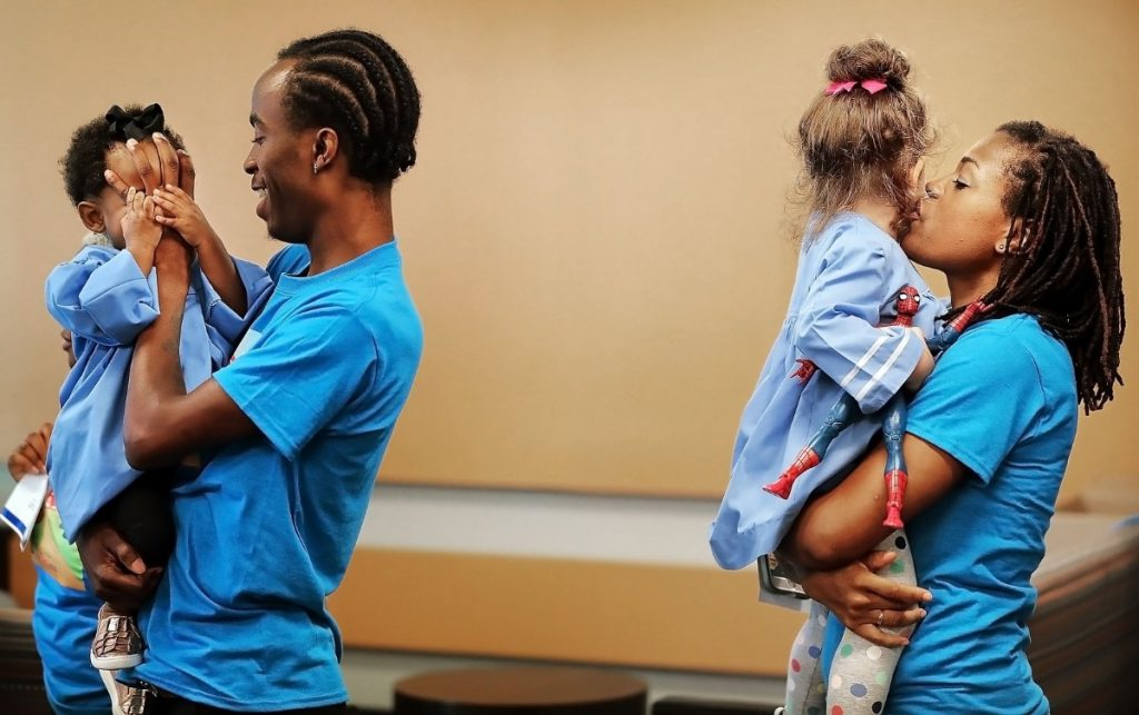 Christian Craine and his daughter Jendaya Craine (left) play while Amelia James gets some affection from her mother Yasmin James during a graduation ceremony at the LeBonheur Children's Hospital community outreach center on Aug. 2, 2019. (Jim Weber/Daily Memphian)