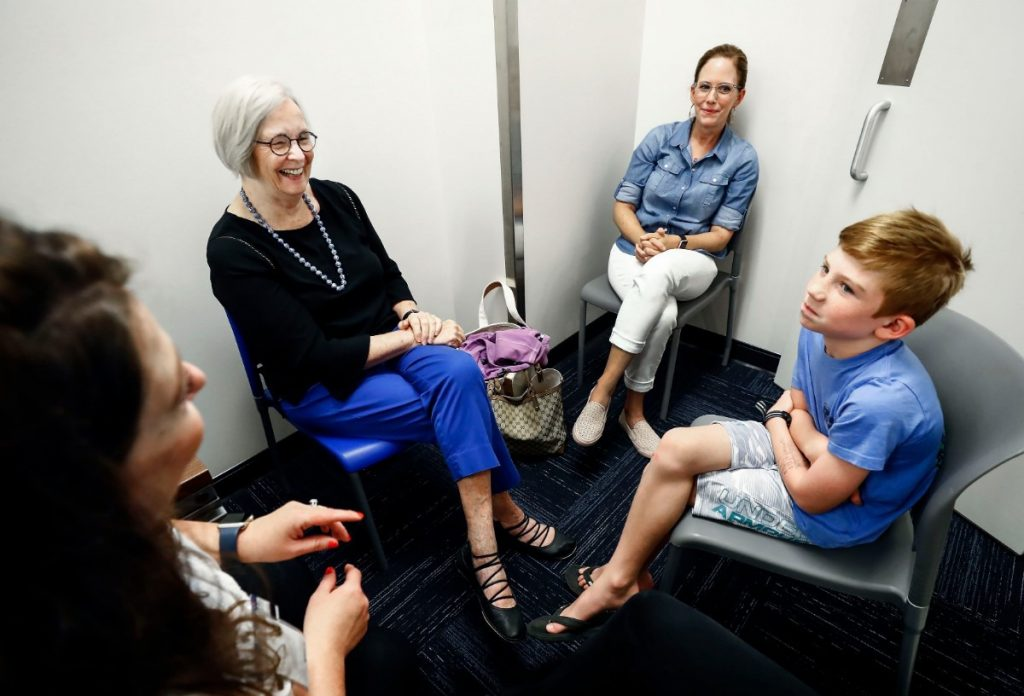 Patient Charlie Wall, 8, (right) along with his mother Rachael Wall (second right) talk with Dr. Deborah Moncrieff (second left) and Dr. Jennifer Taylor (left) after amblyaudia testing at the University of Memphis Speech and Hearing Clinic. They discussed future testing for Charlie, who can hear, but has trouble processing sounds. (Mark Weber/Daily Memphian).
