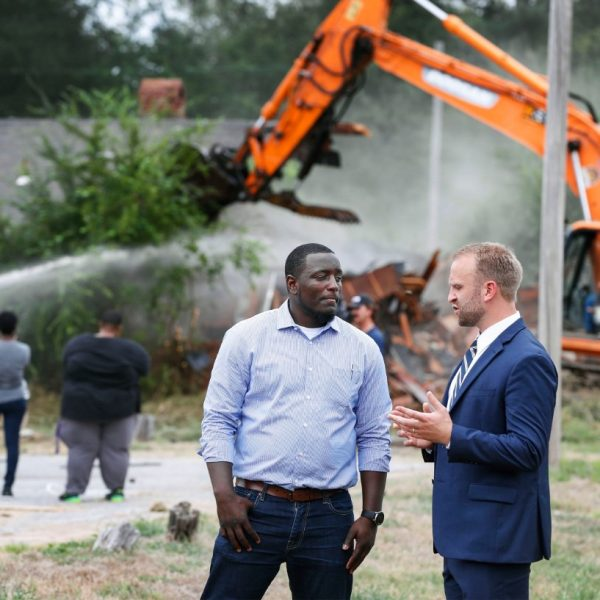 General Contractor Octavius Nickson (left) and Noah Gray, executive director of the Binghampton Development Corp., chat as a bulldozer razes vacant homes on Tillman Cove. during 'Demolition Day' ceremony Sept. 9. (Mark Weber/Daily Memphian file)