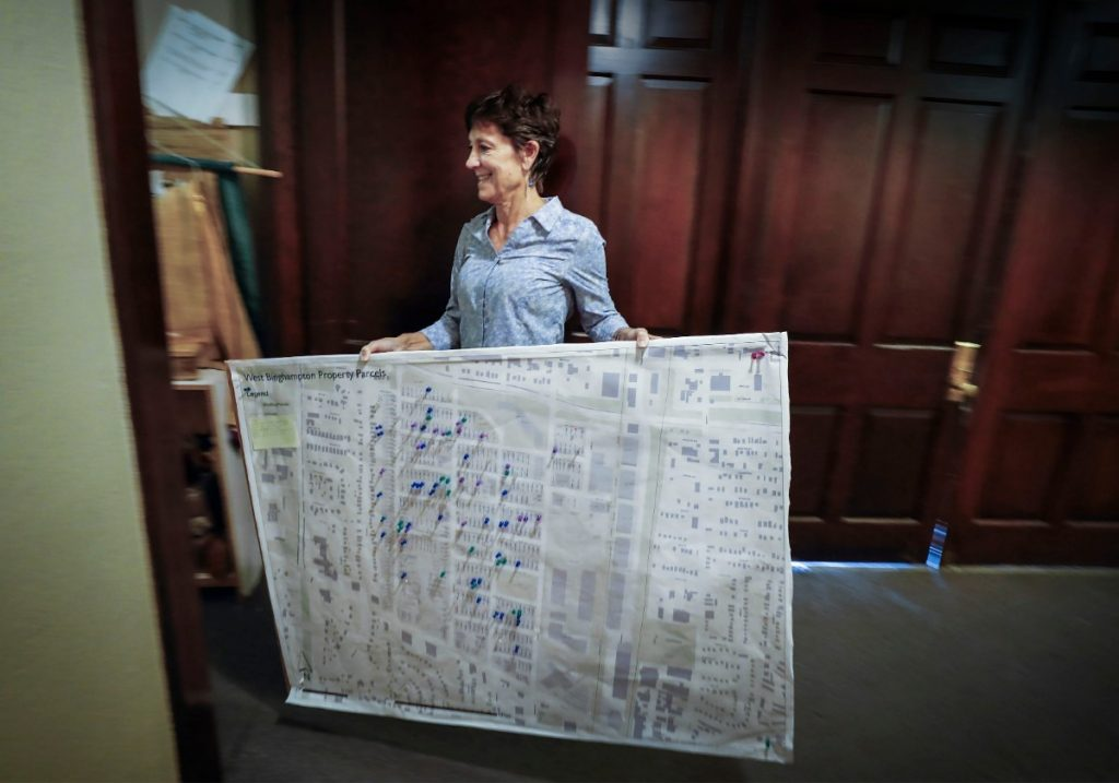 During a meeting of the Binghampton Community Land Trust, resident Joni Laney uses a large map adorned with colored push pins representing the area home recently sold, renovated, for sale or turned into Airbnbs. (Mark Weber/Daily Memphian)