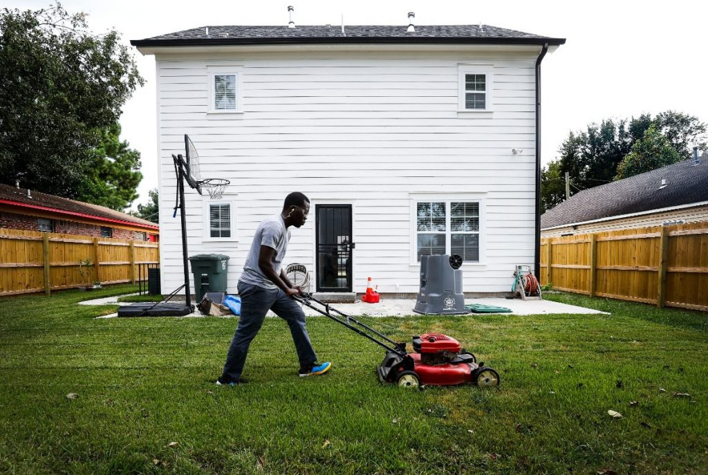 Ceasar Lomo, who moved to Binghampton as a refugee from war-ravaged Sudan in 2001, mows the backyard of his newly purchased home on Princeton Avenue. (Mark Weber/Daily Memphian)