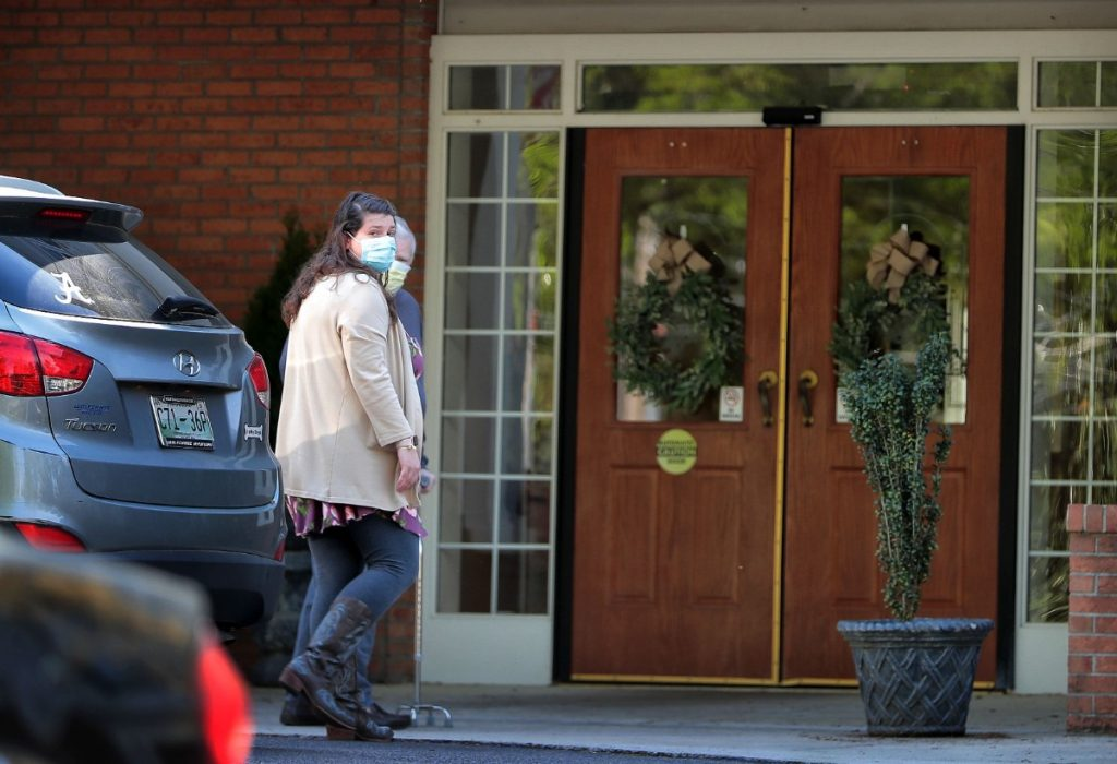 An elderly resident returns home with help from a relative on April 1, 2020, at the Carriage Court assisted living facility in East Memphis where six residents and staff members have tested positive for COVID-19. (Jim Weber/Daily Memphian)