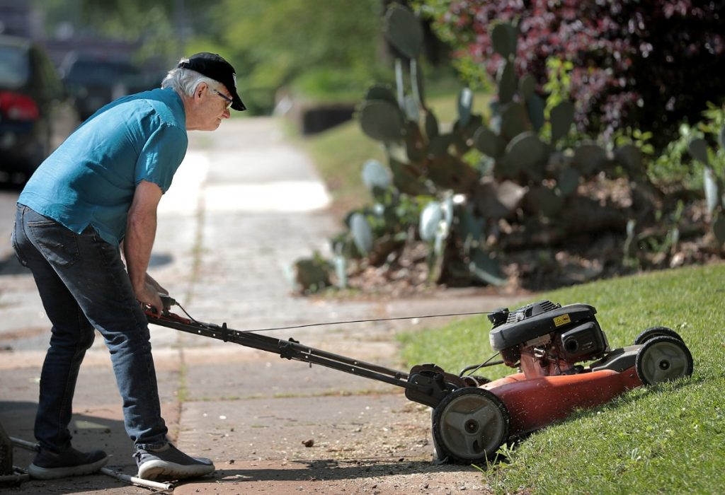 Sam Goff, mowing his home Saturday, April 18, 2020, said says his Midtown neighborhood's  general walkability encourages more foot traffic. (Jim Weber/Daily Memphian)