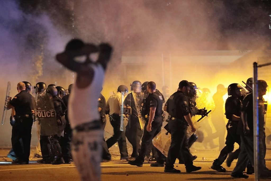 Police retreat June 12, 2019, under a cloud of tear gas as protesters disperse from the scene of a standoff after Frayser residents took to the streets in anger against the shooting a youth identified by family members as Brandon Webber by U.S. Marshals earlier in the evening. (Jim Weber/Daily Memphian)