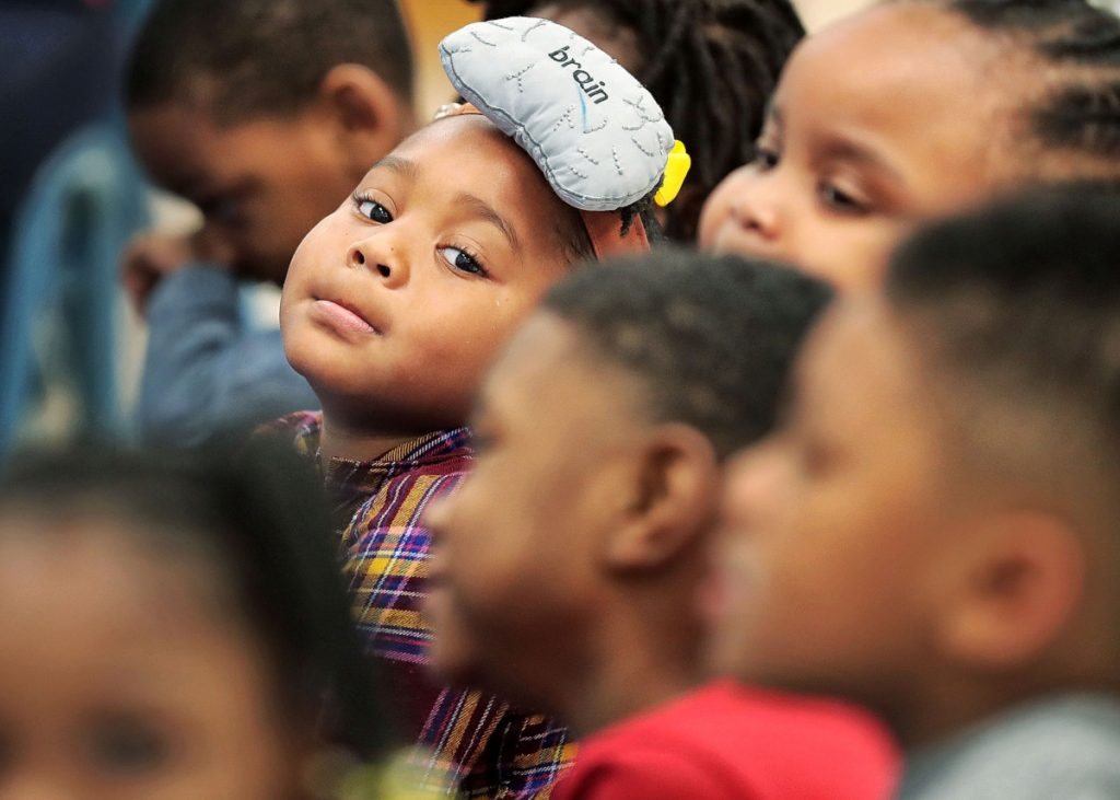 """As a reward, Saimiya Swift, 4, gets to be the """"brain"""" in the class for a day as children read out loud from the board during Alice Holman's pre-K class at Porter-Leath's Douglas Head Start School on April 23, 2019.  (Jim Weber/Daily Memphian)"""