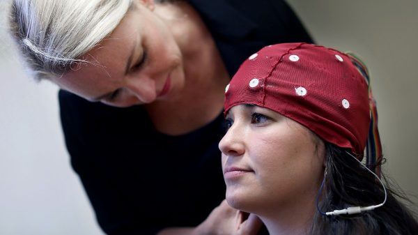 Dr. Eraina Schauss places a cap on the head of Paige Dixon to perform a qEEG (quantitative electroencephalograph), which maps the neural pathways in the human brain. (Patrick Lantrip/Daily Memphian file)