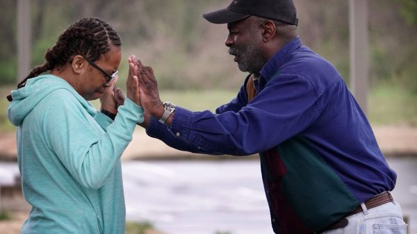 Tonya Jackson (left) prays with church elder Mark Walker at the Holy City Church of God in Christ church in Memphis on March 19, 2020. On Thursday, Memphis Mayor Jim Strickland began to urge places of worship to live stream services while the city is in a state of civil emergency due to the novel coronavirus pandemic. (Karen Pulfer Focht/Special to The Daily Memphian)