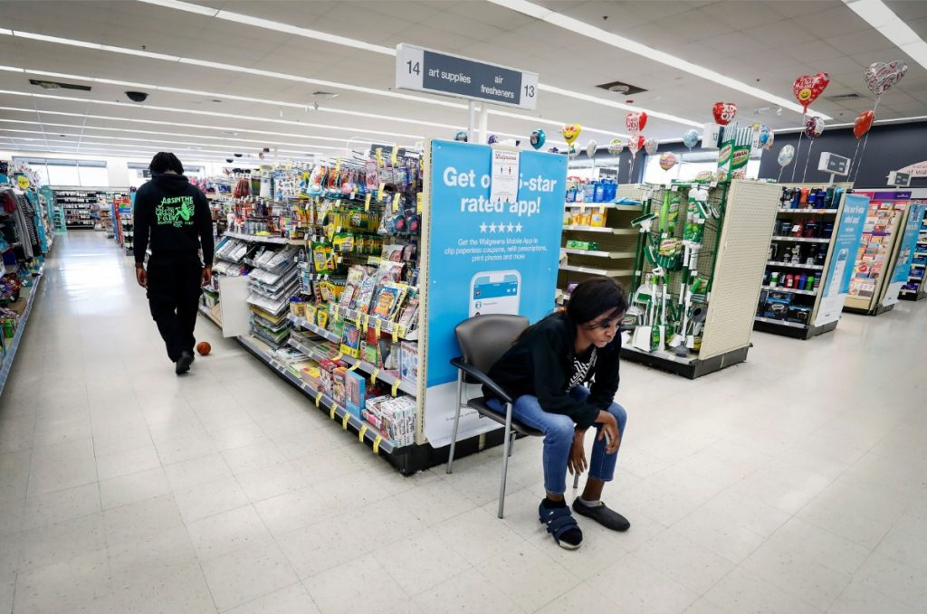 Dinishia Jones (right) sits by herself as her son Therron Farsee Jr. walks the Walgreens aisles on March 24, 2020, while they wait more than an hour for her prescriptions to be filled. Jones recently had surgery on her foot after stepping on a piece of glass while working as a server job at a  Beale Street restaurant. (Mark Weber/Daily Memphian)