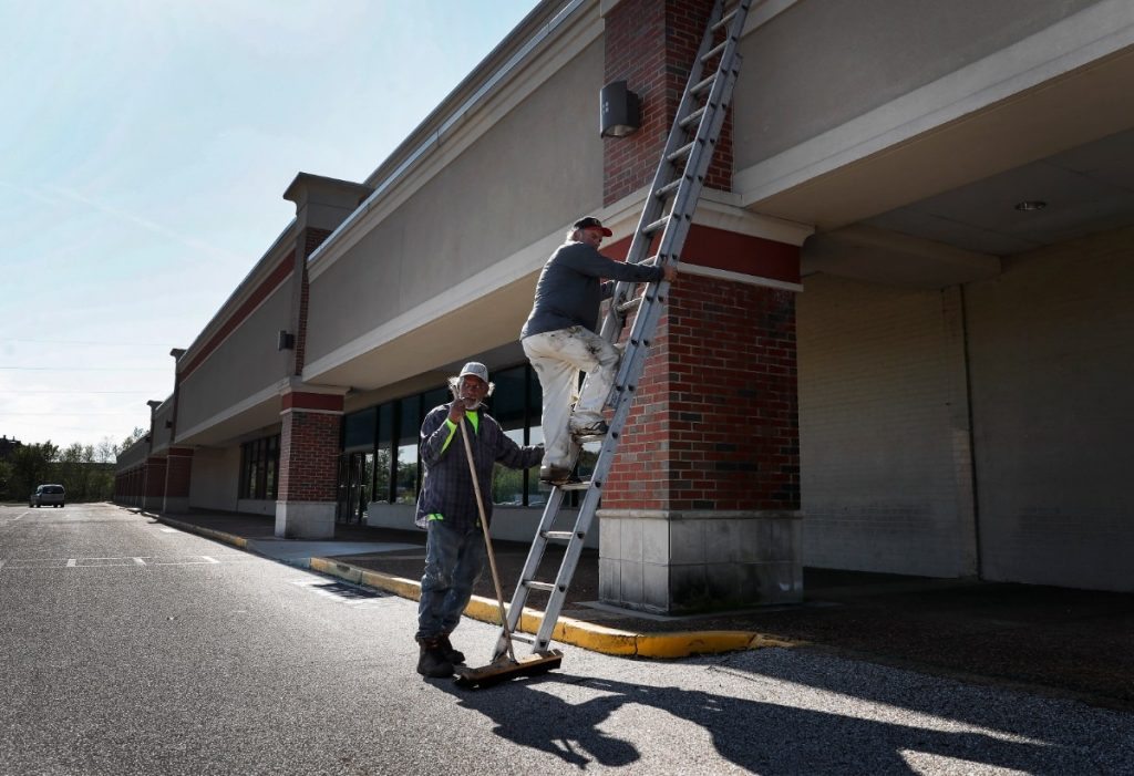 Roofers Larry Dennis (left) and Glenn Janes (right) descend a latter after checking the roof of a vacant rental property in Gateway Shopping Center on Thursday, April 2, 2020. The U.S. Army Corps of Engineers will build a temporary hospital of non-acute beds at the shopping center to help deal with the expected coming surge in COVID-19 cases (Mark Weber/Daily Memphian)