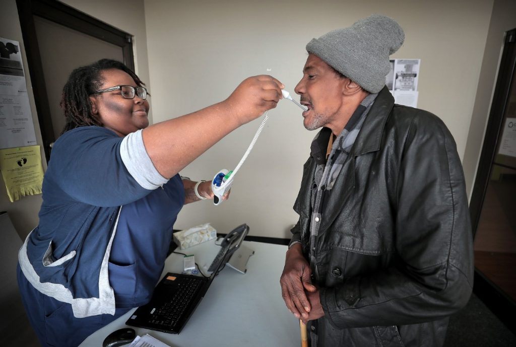 David Stokes (right) gets his temperature taken by Crystal Brown who screens all patients at the Cherokee Healthcare clinic in Frayser on April, 14, 2020 which is providing COVID-19 testing in the neighborhood for current and new patients. (Jim Weber/Daily Memphian)