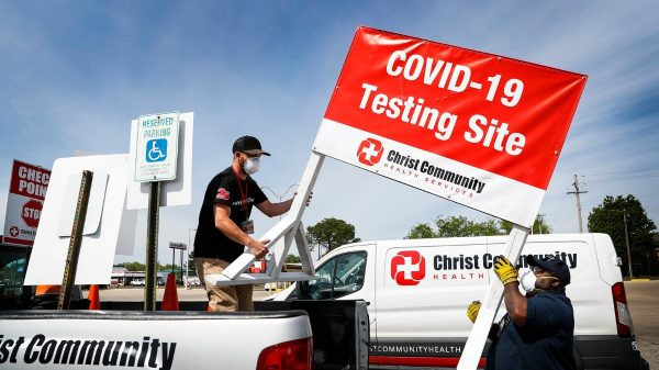 Christ Community Health Services staff members Blake Chastain (left) and Derico Miller (right) set up a drive-thru COVID-19 testing site on April 17, 2020, in the Mendenhall Square Shopping Center. Christ Community will be opening virus testing sites in low-income area of Memphis starting this weekend. (Mark Weber/Daily Memphian)