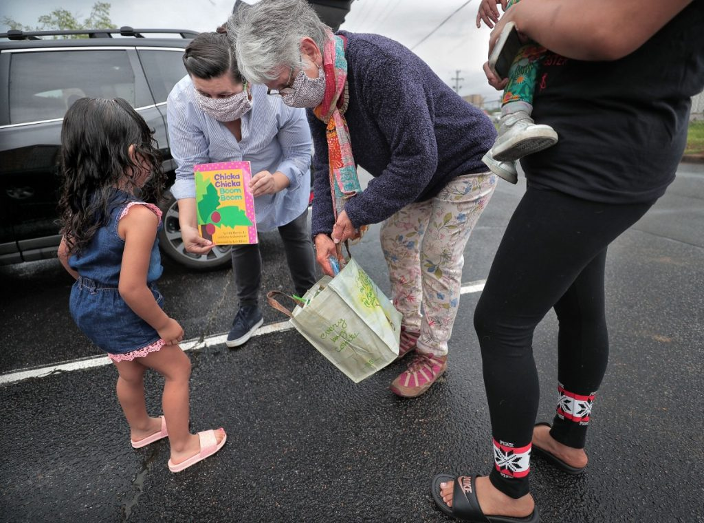 A four-year-old gets a bag of new books from Edith Ornelas (second from left) and Nicole Davila with the Mariposa Collective as the pair delivers care packages of food, clothes and baby supplies to undocumented immigrant families in Southeast Memphis on April 23, 2020. In the midst of the Coronavirus crisis, Ornelas, a cofounder of the collective, and volunteers visit local families several times a week to provide aid. (Jim Weber/Daily Memphian)