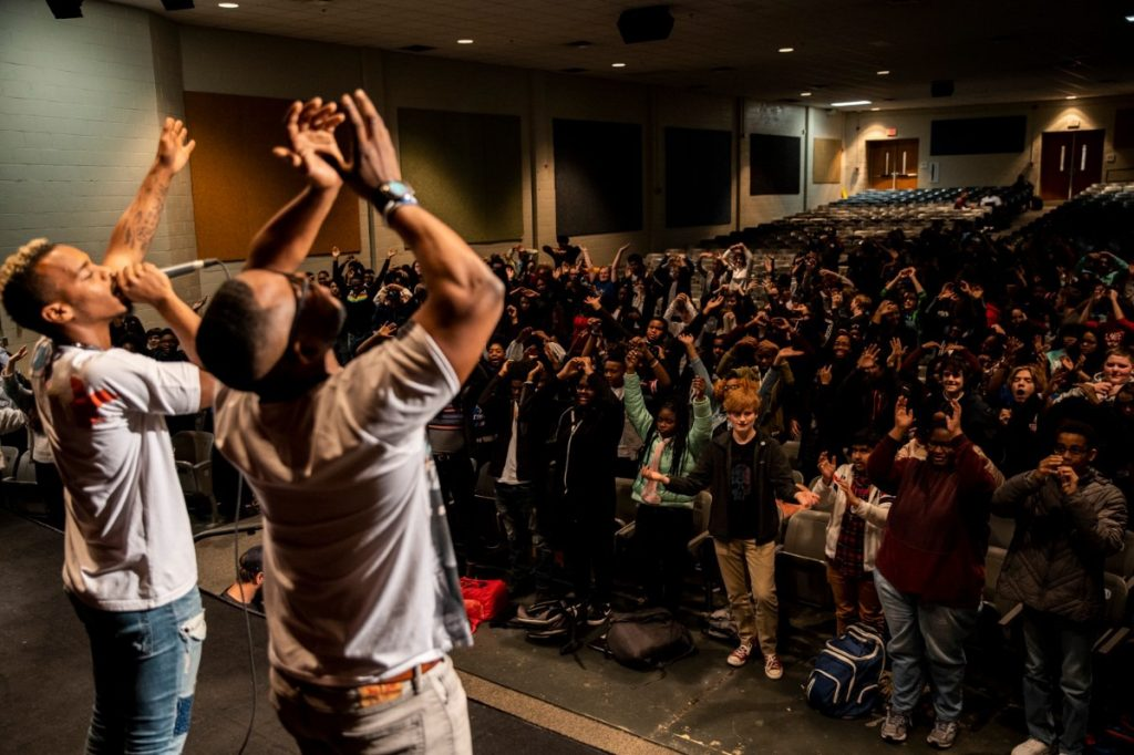 """Grounded team members Lil Buck (left) and Marico """"Dr. Rico"""" Flake (right) share a movement arts exercise to promote peace with students at East High School on January 27th, 2020, during a school-wide engagement with Grounded's film, """"Me and the Light."""" (Photo by Andrea Morales)"""