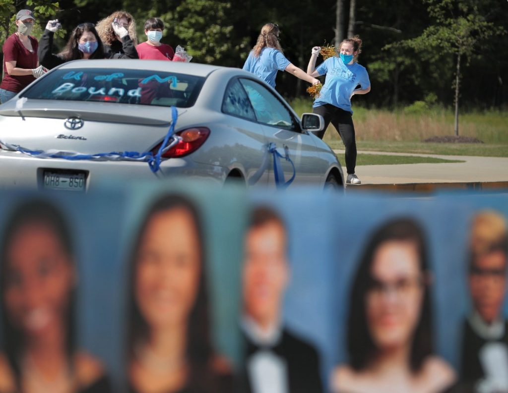 """Volunteers from Collierville First Baptist Church cheer for Collierville High School graduates driving through to pick up their caps and gowns at the school on May 7. """"Going to school can expose children to greater health risks, but so can staying home,"""" said Le Bonheur Children's Hospital pediatrician Jason Yaun. """"Many parents are facing very difficult choices."""" (Daily Memphian file)"""