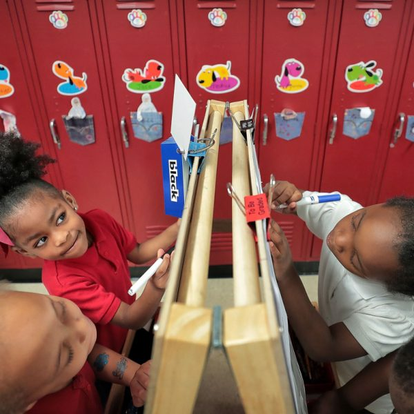 Madison Clark (left), Ayanna Hughes, La'kiya Carr and Jaylen King work at an easel where they color their reading assignment in Thomas Denson's Pre-K class at Cherokee Elementary School. More than three in four Shelby County elementary students, and four in five middle and high school students, read below grade level. (Jim Weber/Daily Memphian)