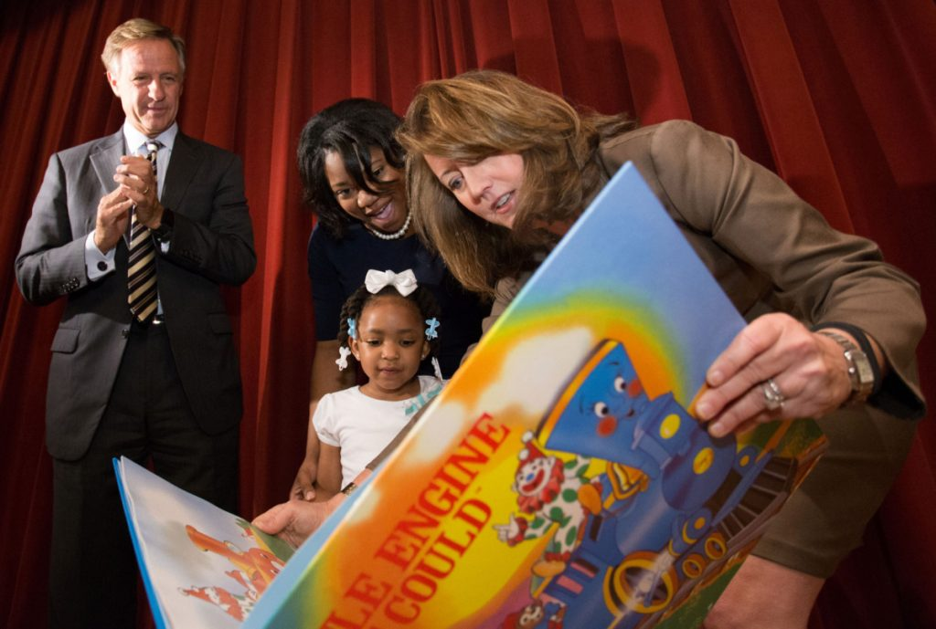 "Crissy Haslam presents Tamera Tynes and her mother, Sierra Tynes, with a copy of ""Little Engine that Could,"" autographed by Dolly Parton, in 2014. In 2016, then-Gov. Bill Haslam and Education Commissioner Candace McQueen launched an early literacy initiative called Read to be Ready. (Daily Memphian file)"