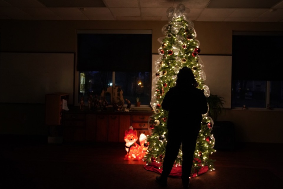 A Memphis victim of domestic violence stands in the glow of a Christmas tree in a Mid-South shelter. She escaped her abuser but is isolated from family over the holidays. Severe cases of domestic violence are on the rise during the pandemic. (Karen Pulfer Focht/Special to Daily Memphian)