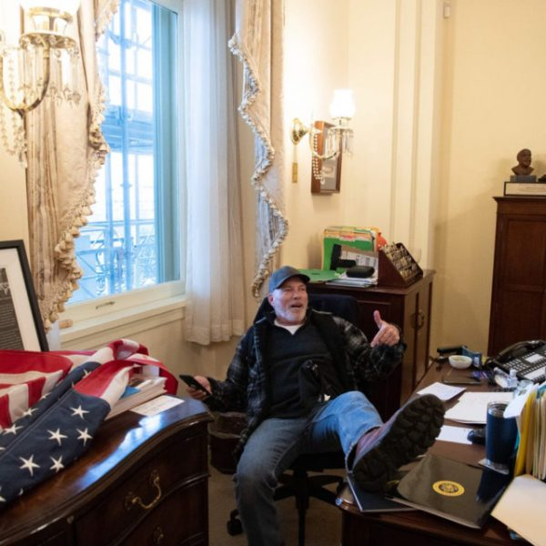 Richard Barnett sits at a desk in House Speaker Nancy Pelosi's office during the Jan. 6 Capitol attack.