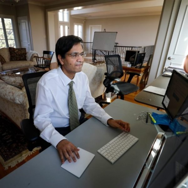 Dr. Manoj Jain answers emails in his home workspace on Wednesday, March 3, 2021. (Mark Weber/The Daily Memphian)