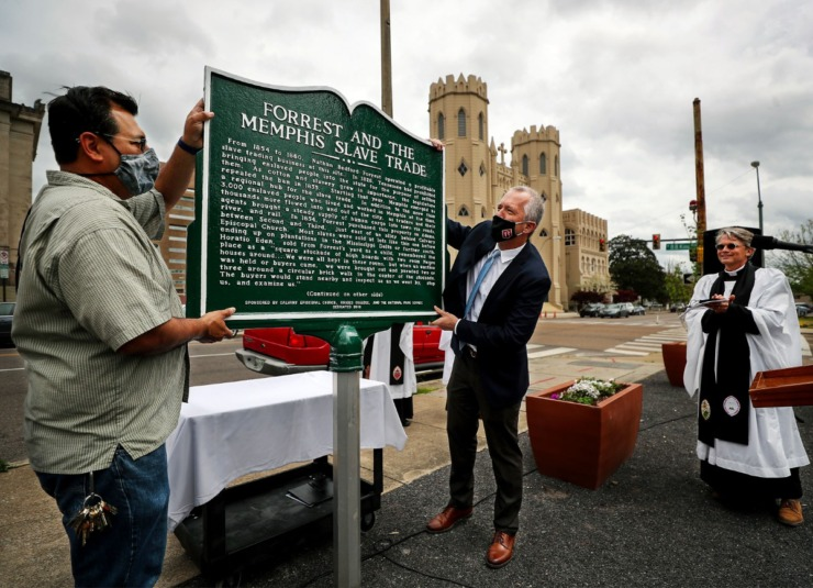 Helario Reyna (left) and Tim Huebner unveil a rededicated plaque outside Calvary Episcopal Church in Downtown Memphis on April 7, 2021. The historical marker notes the location of the Downtown slave market owned by Nathan Bedford Forrest. (Patrick Lantrip/Daily Memphian)